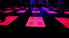 People dance at party in night club with color light on floor Stock Footage