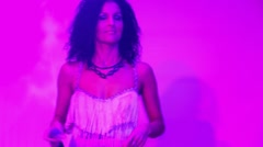 Young woman in white dress sings lit by red light at night club Stock Footage