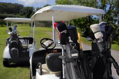 Two golf cart with clubs ready to go Stock Photos