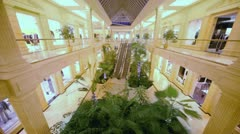 Plants near escalator in hall of shopping center with showcases Stock Footage