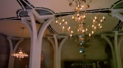 Ceiling with lusters and columns in dark room, shown in motion Stock Footage