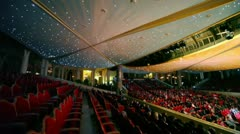 Spectators sit at chairs during concert in huge hall Stock Footage