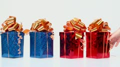 Hand moves four red and blue gift boxes with glisten bows - stock footage