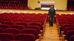 Woman goes between chair rows in hall of huge theater Stock Footage