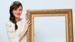 Beautiful woman holds big gilt frame and looks down on it Stock Footage