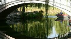 Arch bridge on lake & boat in Yuanmingyuan Park Beijing. Stock Footage