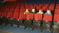 Family of four watching a movie in theater side view Stock Footage