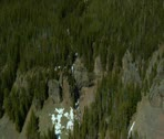 Aerial shot of rocky mountain peaks covered in melting snow Stock Footage