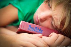 Christian child sleeping with well worn and read bible Stock Photos