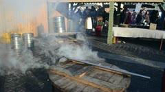 People buy hot drink wine boil huge pots smoke rise fair market Stock Footage