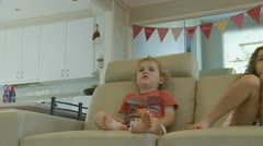 Dolly shot, two children watch TV (4) model release Stock Footage