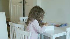 Dolly shot young girl drawing, turns smiling - model release Stock Footage