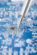 Microcircuit being fixed with soldering iron - stock photo