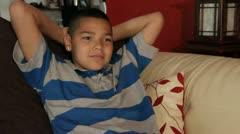 Happy Hispanic boy watches tv on Sofa Stock Footage