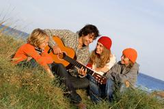 happy family playing guitar in summer holiday - stock photo
