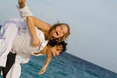 happy piggyback couple on spring break or summer vacation - stock photo