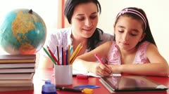 Mother and daughter doing homework on tablet pc Stock Footage