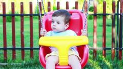 Baby boy in a swing outdoors Stock Footage