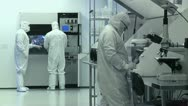 Stock Video Footage of Scientists / Technicians Working in Clean Room, Wide Shot