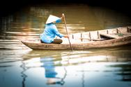 Stock Photo of woman on wooden boat in river in vietnam, asia.