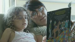 Babysitter reading book to young girl - model release Stock Footage