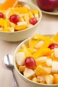 two bowls with fruit salad on wooden table with spoon - stock photo