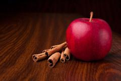 Stock Photo of red apple on dark wooden table with sticks of cinnamon
