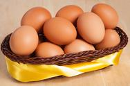 Stock Photo of brown eggs in basket with yellow ribbon