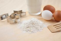 Flour, glass of milk, whisk, cookie cutter forms and eggs on wooden table Stock Photos
