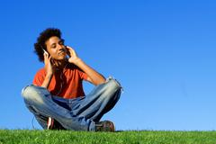 african descent youth listening to music on personal stereo  mp4 or mp3 - stock photo
