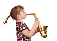 Kaunis pieni tyttö soittaa musiikkia saksofoni Kuvituskuvat