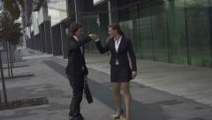 Young business couple fist bump while skateboarding Stock Footage