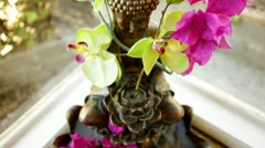 Loop: Buddha fountain in window with pink flowers - high angle - stock footage