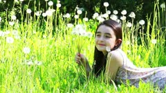 Girl blows flower on meadow Stock Footage