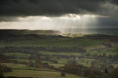 Stock Photo of stunning sun beams over big moor in peak district national park england