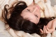 Beautiful and sexy young woman laying on the fur coat. Stock Photos