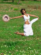 Happy healthy young woman jumping in summer or spring Stock Photos