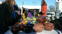 Stock Video Footage of young woman sell handmade crockery clay pots crafts market fair