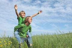 Healthy happy fit active kids playing piggyback outside in summer Stock Photos