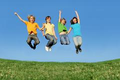 Fit healthy children jumping outdoors in summer Stock Photos