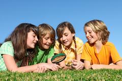 Stock Photo of kids at summer camp playing with magnifying glass