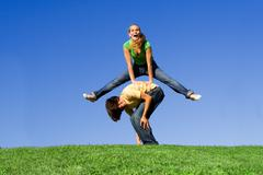 Active teens playing leapfrog Stock Photos