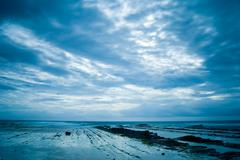 rocky seacoast with heavy clouds - stock photo