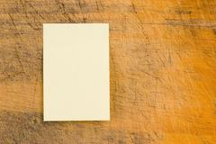 Stock Photo of yellow note paper on retro wood