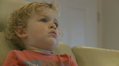 Side profile of boy watching TV mid shot (2) model release Stock Footage