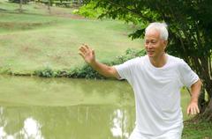 Kiinalainen vanhempi suoriutuneen taiji vihreä ulkona Kuvituskuvat