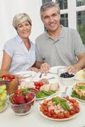 Middle aged couple healthy eating salad table Stock Photos