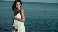 Pregnant woman standing on the seashore, slow motion shot at 120fps - stock footage