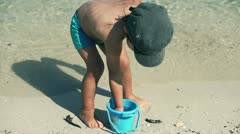 Little boy with plastic pail playing on the beach, slow motion shot at 240fps - stock footage