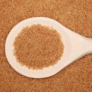 Brown sugar on a wooden spoon Stock Photos